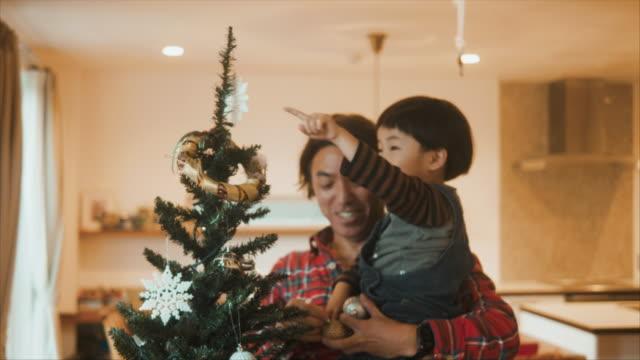 stockvideo's en b-roll-footage met de japanse vader verfraait kerstboom met zijn kinderen - christmas family