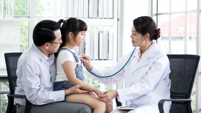 日本の女性医師が聴診器によって父の膝の上に座っているタイの女の子を調べる - 聴診器点の映像素材/bロール