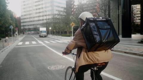 vídeos de stock e filmes b-roll de japanese female food courier delivering orders in tokyo (slow motion) - food