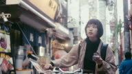istock Japanese female food courier looking for the delivery address in Tokyo (slow motion) 1204175680