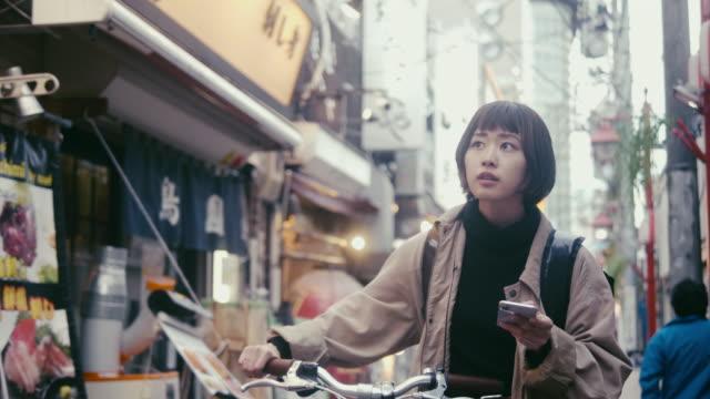 japansk kvinnlig mat kurir letar efter leveransadress i tokyo (slow motion) - japan bildbanksvideor och videomaterial från bakom kulisserna