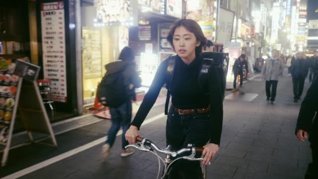 vidéos et rushes de courrier alimentaire féminin japonais recherchant l'adresse de livraison à tokyo (mouvement lent) - 20 24 ans