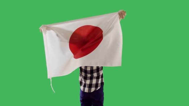 A Japanese flag on the back of a child on chroma key green screen.