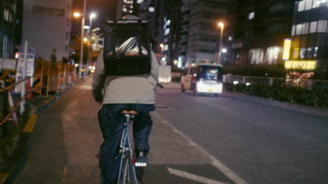 japanese food courier cycling in the night (slow motion) - food delivery filmów i materiałów b-roll