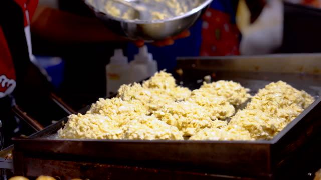 japon yemekleri, okonomiyaki, un, ekmek kırıntısı ve diğer maddeler ve sonra kızarmış. - hiroshima stok videoları ve detay görüntü çekimi