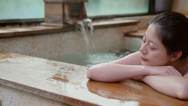 japansk flicka tar en vila liggande på vid poolen - japanese bath woman bildbanksvideor och videomaterial från bakom kulisserna