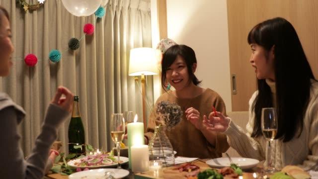 vidéos et rushes de filles japonaises en savourant des plats de noël - diner entre amis