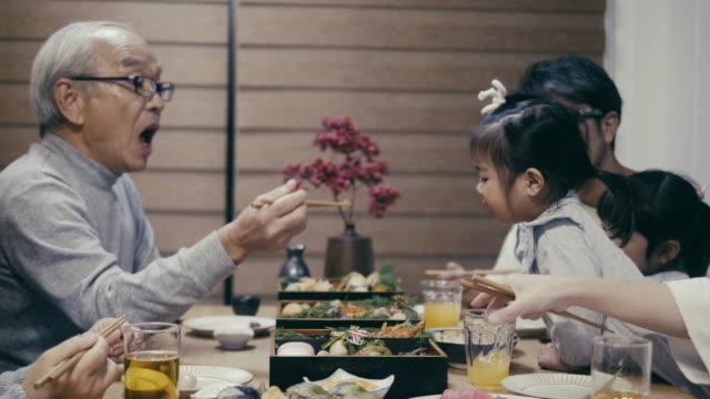 nonno giapponese che nutre i nipoti la sera di capodanno - cultura orientale video stock e b–roll
