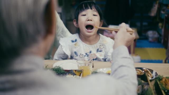 japanese grandfather feeding grandchildren on new year's eve - кормить стоковые видео и кадры b-roll