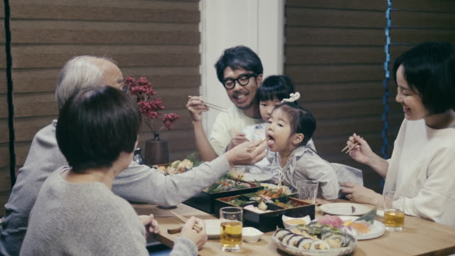 japanese grandfather feeding grandchildren on new year's eve - cultura orientale video stock e b–roll