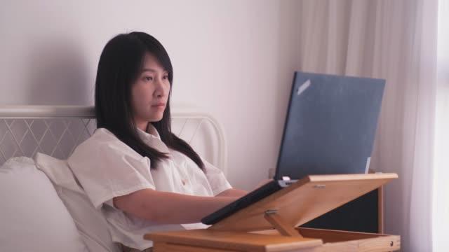 日本のジャーナリストは彼女の寝室フリーランサーの自宅で仕事でノート パソコンを使用して彼女の仕事を入力します。 ビデオ