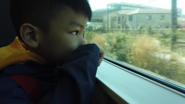 日本の子供は外の世界に列車の外を見ている - 乗客点の映像素材/bロール