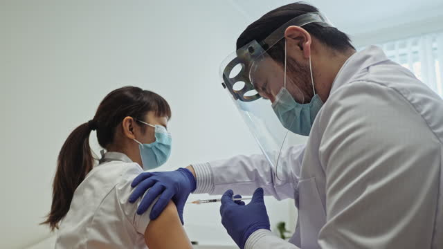 Japanese male doctor vaccinates female nurse Vaccination and hospital series with a male doctor and female nurse. estonia stock videos & royalty-free footage