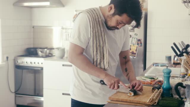 日本人男性が巻寿司を切る(スローモーション) - 自家製点の映像素材/bロール
