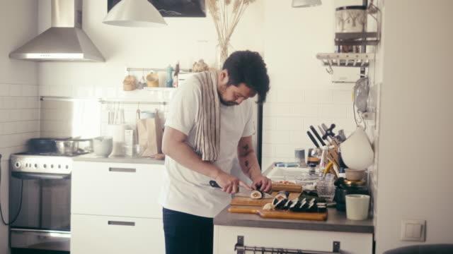 vidéos et rushes de homme japonais coupant le sushi de maki (mouvement lent) - cuisine non professionnelle