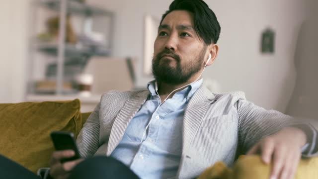 vídeos de stock, filmes e b-roll de homem japonês ouve podcast - podcast