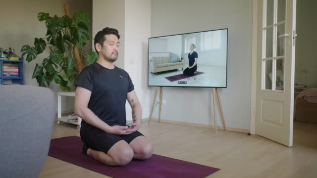 Japanese man meditates during a yoga online session at home Video series of stay-at-home fitness during lockdown in self isolation. mindfulness stock videos & royalty-free footage