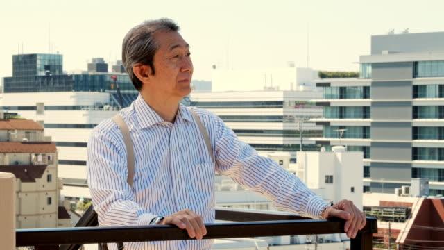 バルコニーに日本人男性 - シニア点の映像素材/bロール