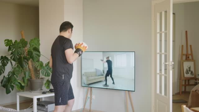 孤立したロックダウン中にオンラインボクシングのレッスンを受ける日本人男性 - テレビ会議 日本人点の映像素材/bロール