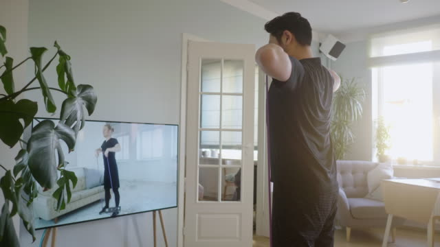 Japanese man taking online fitness lessons during lockdown in isolation