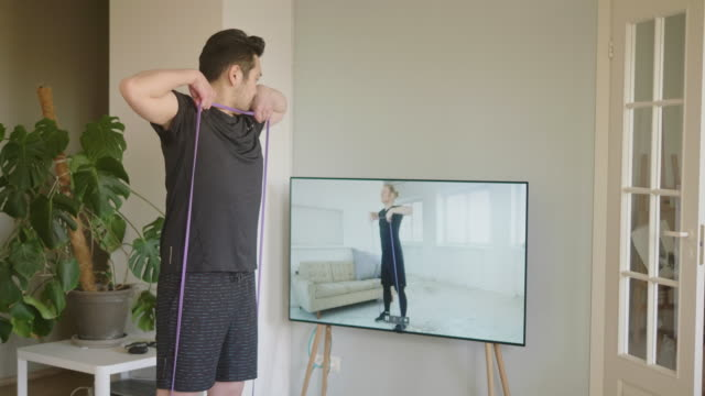 japanese man taking online resistance band fitness lessons during lockdown in isolation - kurs ćwiczeń filmów i materiałów b-roll