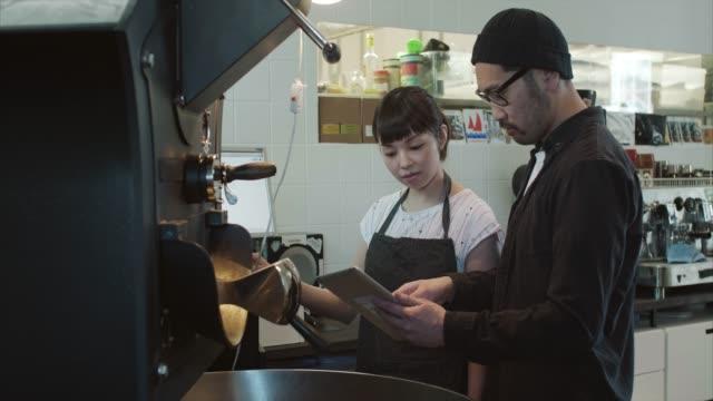 日本人男性は、見習いロースト コーヒー (スローモーション) する方法を教える - カフェ文化点の映像素材/bロール