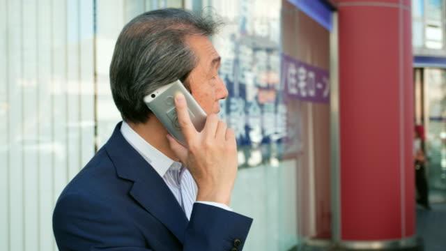 Japanese Man using Telephone video