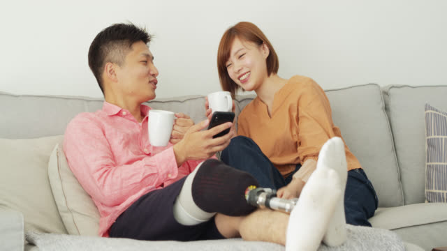 Japanese Man with Prosthetic Leg Drinking Coffee with Girlfriend at Home A young Japanese couple relaxing together at home. He has a prosthetic leg. artificial limb stock videos & royalty-free footage