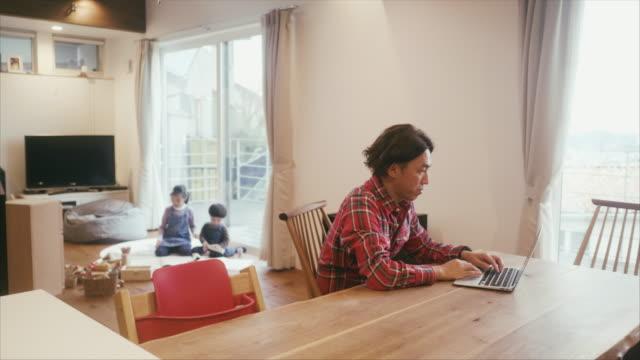 日本人男性は、子どもたちが居間で遊んでいる間、自宅で働いています - パソコン 日本人点の映像素材/bロール