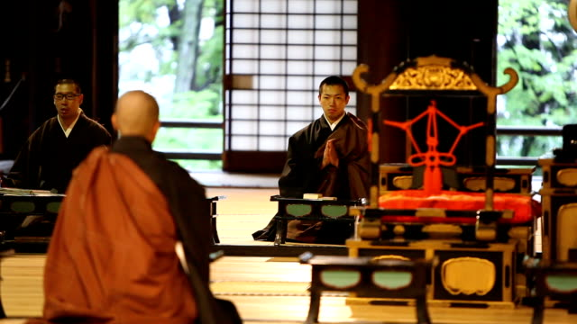 japanese monks praying in a buddhist temple - buddha video stock e b–roll