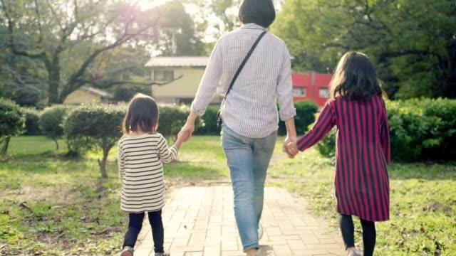 手をつないで公園を歩く日本人の両親と姉妹 - 後ろ姿点の映像素材/bロール