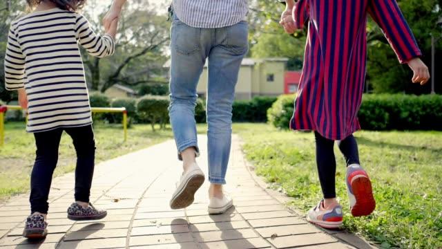 手をつないで公園を歩く日本人の両親と姉妹 - 親族会点の映像素材/bロール