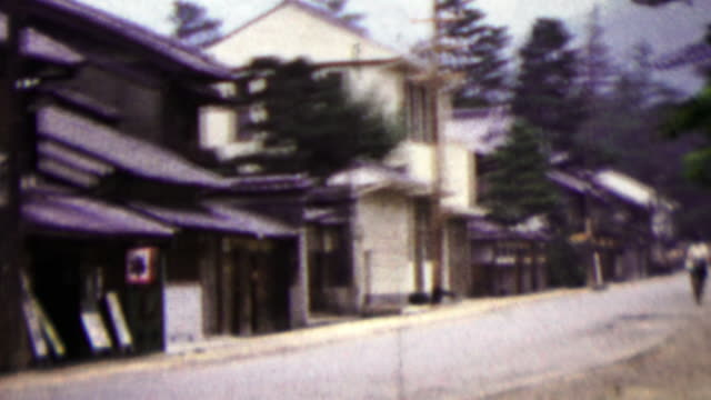 1951: Japanese quiet street woman riding bike in distance. video