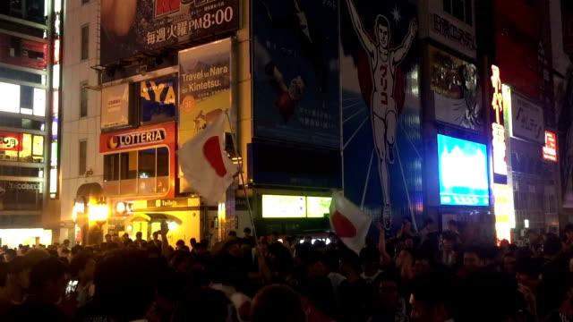 japanese soccer fans celebrating at dotonburi bridge in osaka , japan . - 2018 video stock e b–roll