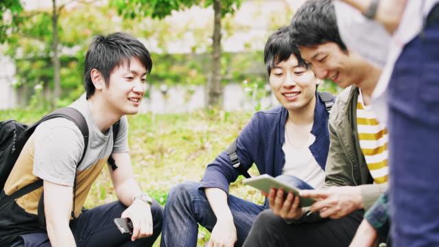 vidéos et rushes de étudiants japonais ws détente dans le parc - culture japonaise
