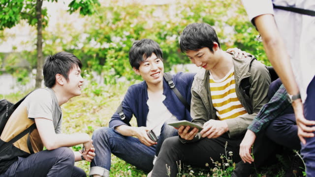 ws japanese students using digital tablet in the park - student life stock videos & royalty-free footage