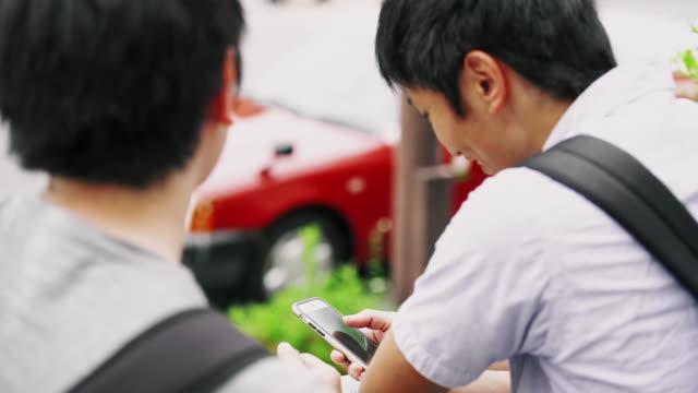 CU の日本人学生がバスを待っている間にスマート フォンを使用して ビデオ