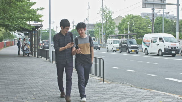 japanese students walking in the street checking their mobile phones - two students together asian video stock e b–roll