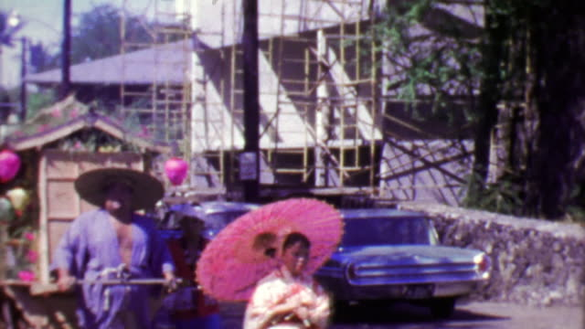 1964: Japanese style parade man pulling traditional merchant cart. video
