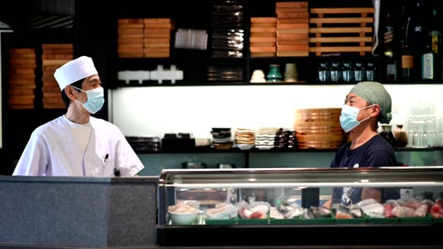 Japanese sushi chefs wearing a masks for Covid-19 Reopening protocol at a sushi restaurant for the coronavirus pandemic. Hygiene and sanitation in restaurants. opening event stock videos & royalty-free footage