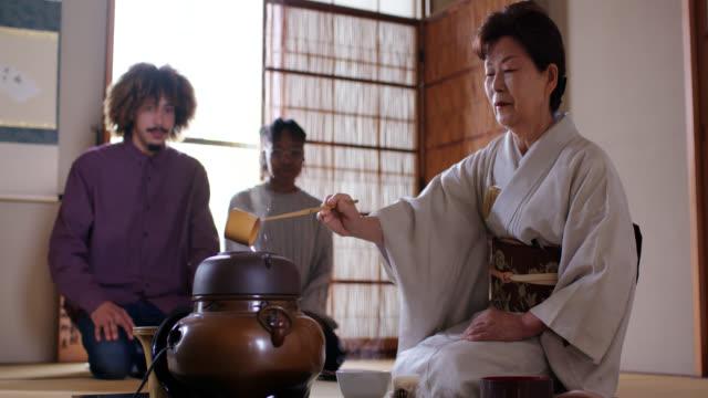 日本茶マスターは2人の観光客のためにお茶を作る - アフリカ民族点の映像素材/bロール