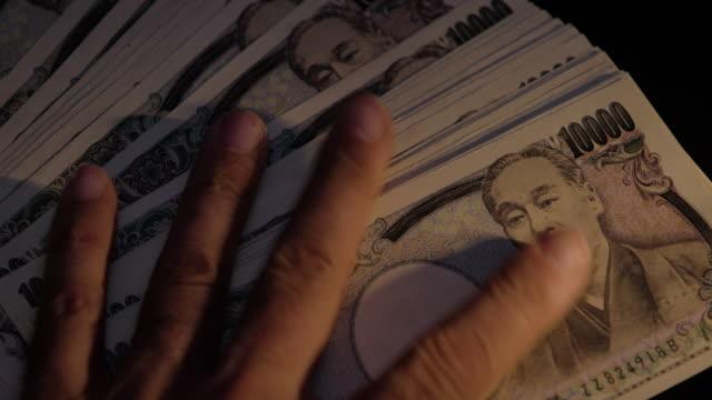 stockvideo's en b-roll-footage met japanse tienduizend yen rekeningen uitwaaierde op een tafel, close-up, licht fade up - yenteken