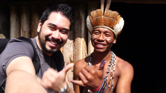 japanese tourist taking a selfie with indigenous brazilian man, from guarani ethnicity - south america travel stock videos and b-roll footage
