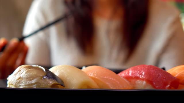 Japanese woman eating sushi Japanese woman eating sushi tuna seafood stock videos & royalty-free footage