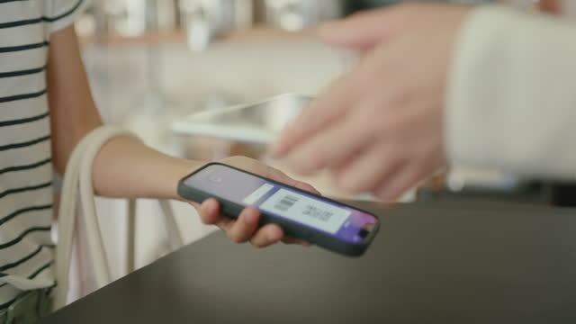 持続可能な店でスマートフォンで支払うcu-日本の女性 - クレジット決済点の映像素材/bロール