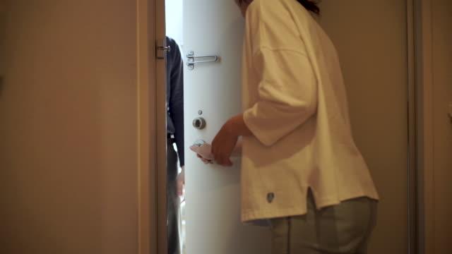 ön kapıda teslim bir kağıt torba alan japon kadın - sahanlık stok videoları ve detay görüntü çekimi
