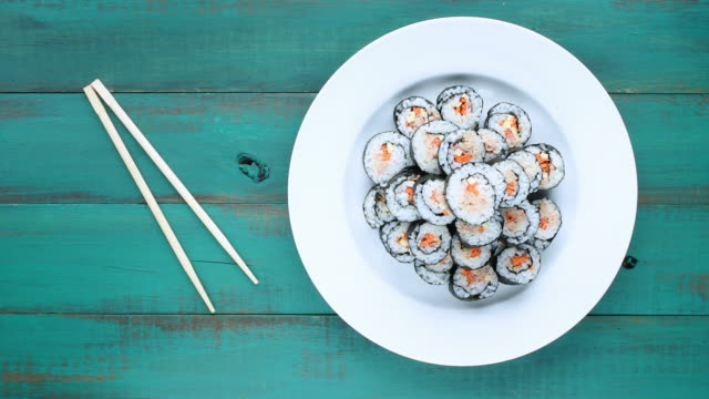 Japanese woman serve homemade Sushi maki gunkan roll plate Japanese woman serve homemade Sushi maki gunkan roll plate. Served in Japanese bar restaurant. Top view, flat lay. Food background. copy space. sashimi stock videos & royalty-free footage