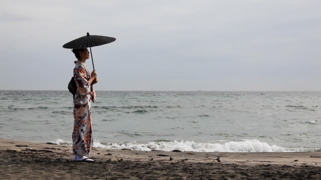 japanische frau stehend am meer - sonnenschirm stock-videos und b-roll-filmmaterial