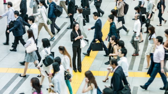 Japanese woman talking on the mobile phone surrounded by commuters Japanese woman talking on the mobile phone surrounded by commuters walking to work. individuality stock videos & royalty-free footage