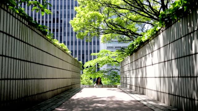 日本の女性が公園の散歩、東京で - 緑 ビル点の映像素材/bロール